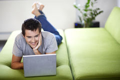 Junger Mann mit Lapot liegend auf einem Sofa. Young man with a laptop, laying on a bed © i love images - Fotolia.com